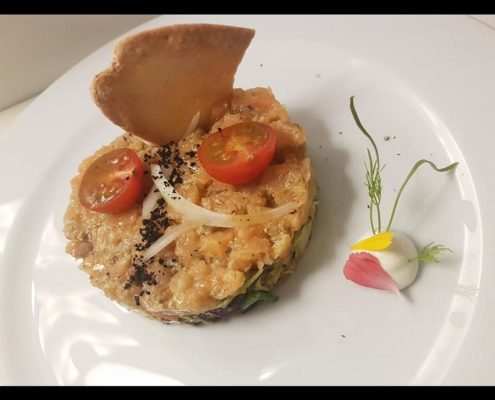 dish of salmon tartare with soy and capers and lemon Cinnamon Restaurant