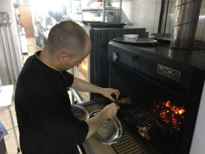 Grana chef cooking in oven burning ember ecologica