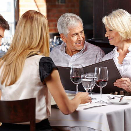 22649020 - family with two senior people in restaurant holding the menu